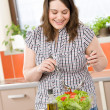 Cook - Plus size happy woman preparing salad in kitchen — Stock Photo #4684304