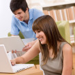 Student - two teenager with laptop in living room - ストック写真