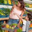 Grocery store shopping - Woman with child buying vegetable — Stock Photo