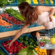 Stock Photo: Grocery store shopping - Young woman buying vegetable