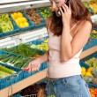 Grocery store shopping -  Woman holding mobile phone — Stock Photo