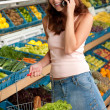 Grocery store shopping - Smiling woman with mobile phone — Stock Photo