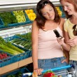 Grocery store shopping - Two women with mobile phone — Stock Photo