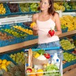 Grocery store shopping - Young woman choosing pepper — Stock Photo
