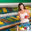 Stock Photo: Grocery store shopping - Womholding two peppers