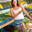 Grocery store shopping - Young woman with mobile phone — Stock Photo