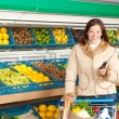 Grocery store shopping - Smiling woman with mobile phone - Lizenzfreies Foto