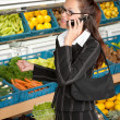 Grocery store shopping - Business woman with mobile phone — Stock Photo