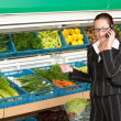 Stock Photo: Grocery store shopping - Business woman with mobile phone
