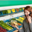 Grocery store shopping - Red hair woman with mobile phone - Lizenzfreies Foto