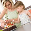 Mother and child with chocolate cake in kitchen - Stock Photo