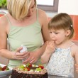 Stock Photo: Mother and child with chocolate cake in kitchen