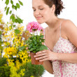 Gardening - woman holding flower pot smelling flower — Stock Photo