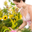 Gardening - woman with watering can and flowers — Stockfoto