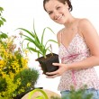 Gardening - woman holding flower pot, watering can — Stock Photo