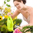 Gardening - woman with watering can and flowers — Стоковая фотография