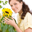 Smiling woman holding flower pot with sunflower — Stock Photo #4684747