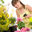 Gardening - smiling woman with flower and sprinkler — Stock Photo