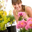 Gardening - smiling woman with flower — Stock Photo