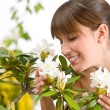 Portrait of woman smelling blossom of Rhododendron flower - Stock Photo