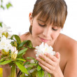 Portrait of woman smelling blossom of Rhododendron — Stock Photo #4684815