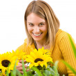 Gardening - portrait of smiling woman with sunflowers — Stock Photo #4684880