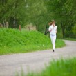 Jogging - sportive woman running on road in nature — Stock Photo #4684883