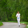 Jogging - sportive woman running on road in nature — Stock Photo