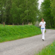 Jogging - sportive woman running on road in nature — Stock Photo #4684902