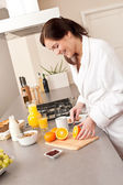 Young woman in bathrobe cutting orange in kitchen — Stock Photo