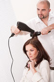 Professional hairdresser with hair dryer at salon with customer — Stock Photo