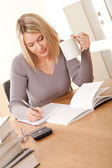 Student series - Blond girl writing homework — Stock Photo