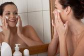 Tělo péče série - mladá žena použitím krém v koupelně — Stock fotografie