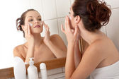 Body care series - Beautiful young woman applying cream — Stock Photo
