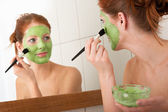 Body care series - Young woman applying facial mask — Stok fotoğraf