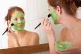 Serie del cuidado del cuerpo - joven aplicar mascarilla facial — Foto de Stock
