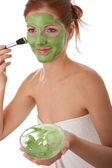Body care series - Attractive woman applying green facial mask — Stock Photo