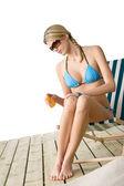 Beach - Young woman in bikini apply suntan lotion — Stock Photo