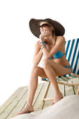 Beach - Young woman in bikini sitting on deck chair — Stock Photo
