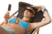 Beach - Attractive woman with hat and ice lolly — Stock Photo