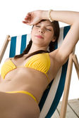 Beach - Beautiful woman sunbathing in bikini on deckchair — Stock Photo