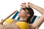 Beach - Woman with ear buds sunbathing in bikini — Stock Photo