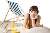 Beach with deck chair - Woman in bikini sunbathing — Stock Photo