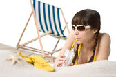 Beach - Woman in bikini with drink and flip-flop on sand — Stock Photo