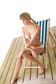 Beach - Woman in bikini sunbathing on deck chair — Stock Photo