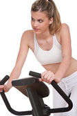 Fitness series - Young woman on exercise bike — Stock Photo