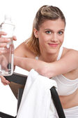 Fitness series - Woman with exercise bike and bottle of water — Stock Photo