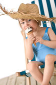 Beach - Little girl on deck-chair with hat and ice-cream — Stock Photo