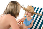 Mother with child apply suntan lotion on beach — Stock Photo