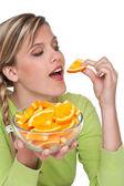 Healthy lifestyle series - Woman eating orange — Stock Photo